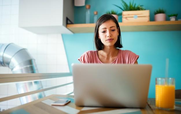 Gelukkig casual mooie vrouw werken, studeren, surfen, winkelen op een laptop