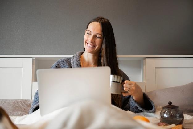 Gelukkig casual mooie vrouw werkt op een laptop zittend op het bed in het huis.