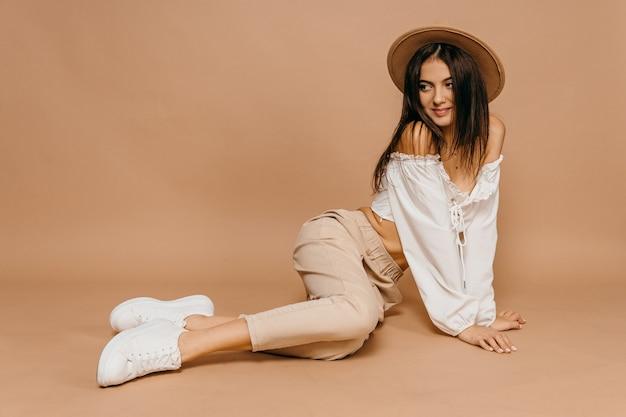 Gelukkig casual vrouw liggend op de vloer met mooie haat over pastel achtergrond. dame, schattig. provence concept. hoge kwaliteit foto