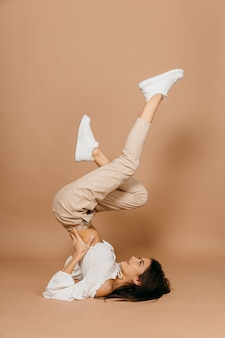 Gelukkig casual vrouw liggend op de vloer met opgeheven benen omhoog over pastel achtergrond. dame, schattig. hoge kwaliteit foto