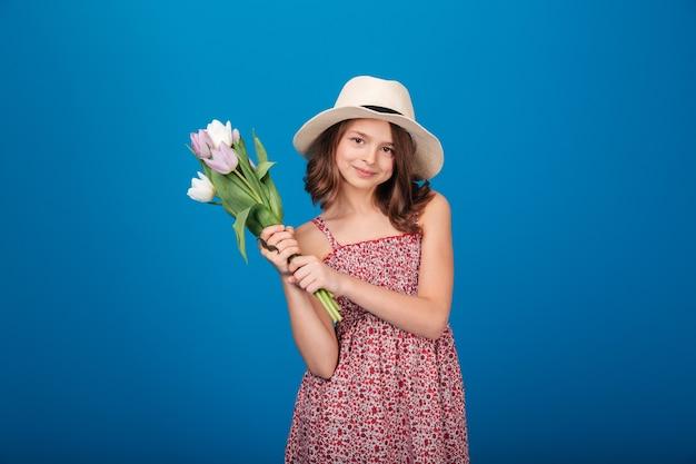 Gelukkig charmant meisje dat een boeket tulpen op een blauwe achtergrond vasthoudt en staande houdt
