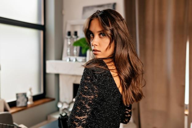 Gelukkig charmant meisje gekleed zwarte glans jurk glimlachend in de woonkamer