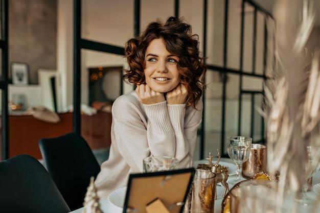 Gelukkig charmant meisje met krullend kapsel glimlachend met gelukkige emoties wachten op kerstmis