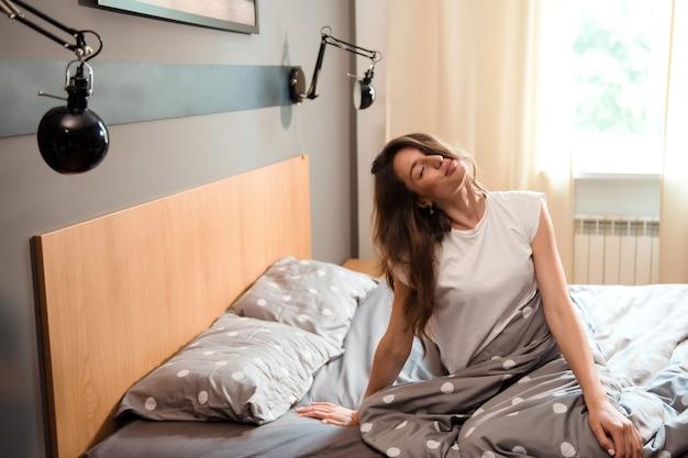 Gelukkig charmant meisje met lang donker haar dat het lichaam in bed uitrekt na het wakker worden