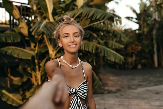 Gelukkig charmante blonde vrouw in gestreepte zwart-witte jurk en met parel ketting glimlacht en houdt iemands arm in tropisch park