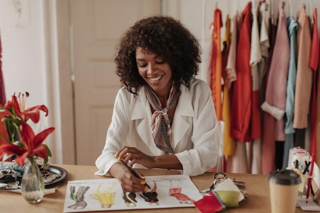 Gelukkig charmante brunette krullende vrouw in trendy witte blouse en zijden sjaal glimlacht en ontwerpt nieuwe mode kleding op kantoor