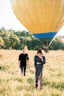 Gelukkig charmante jonge vrouw in modieuze zwarte kleding, permanent in mooie zomerse groene veld, terwijl haar vriendje naar haar loopt