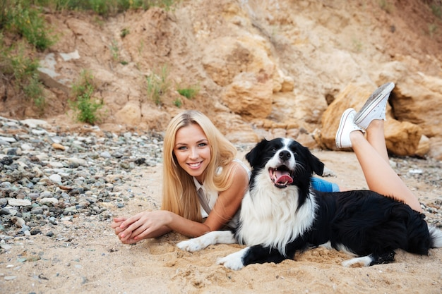 Gelukkig charmante jonge vrouw met hond op het strand