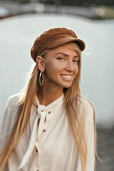 Gelukkig charmante vrouw in stijlvolle katoenen blouse en trendy bruine pet glimlacht breed en loopt in een goed humeur naar buiten