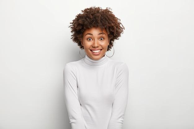 Gelukkig charmante vrouw met afro kapsel, draagt sneeuwwitte poloneck trui, in goed humeur na het winkelen
