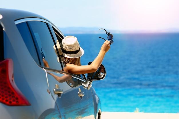 Gelukkig chauffeursmeisje in auto op zee in de zomer