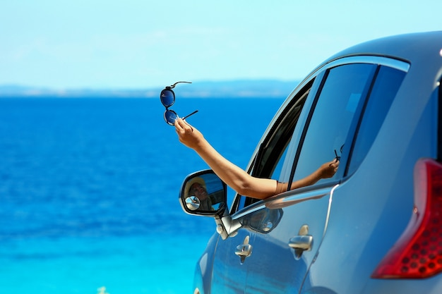 Gelukkig chauffeursmeisje met zonnebril in auto op zee in de zomer