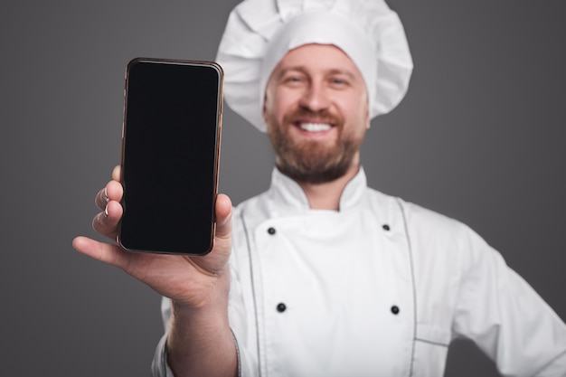 Gelukkig chef-kok smartphone tonen op camera