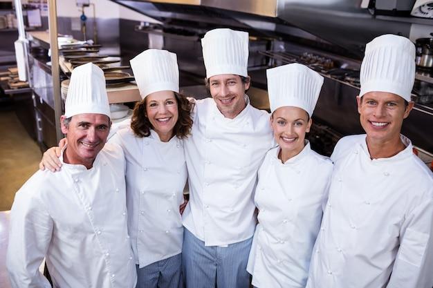Gelukkig chef-koksteam die zich in commerciële keuken verenigen