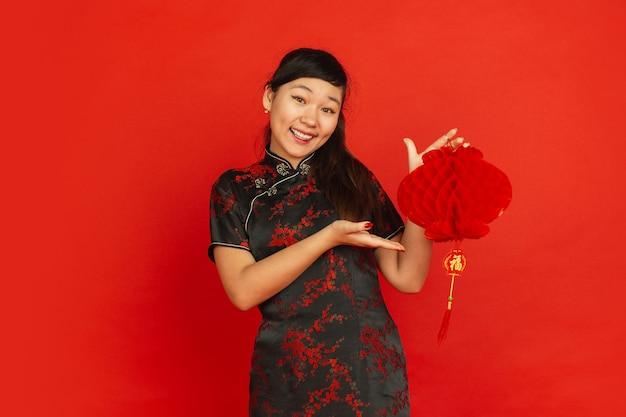 Gelukkig chinees nieuwjaar 2020. het portret van het aziatische jonge meisje dat op rode achtergrond wordt geïsoleerd. vrouwelijk model in traditionele kleding ziet er gelukkig uit en lacht met decoratie. viering, vakantie, emoties.
