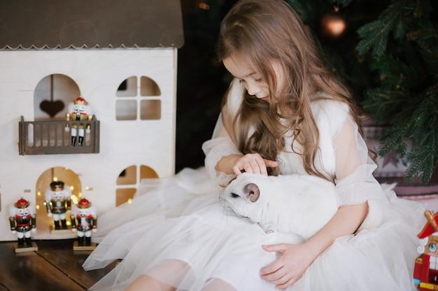 Gelukkig chinees nieuwjaar 2020 jaar van rat. portret van schattige witte chinchilla op de achtergrond van de kerstboom
