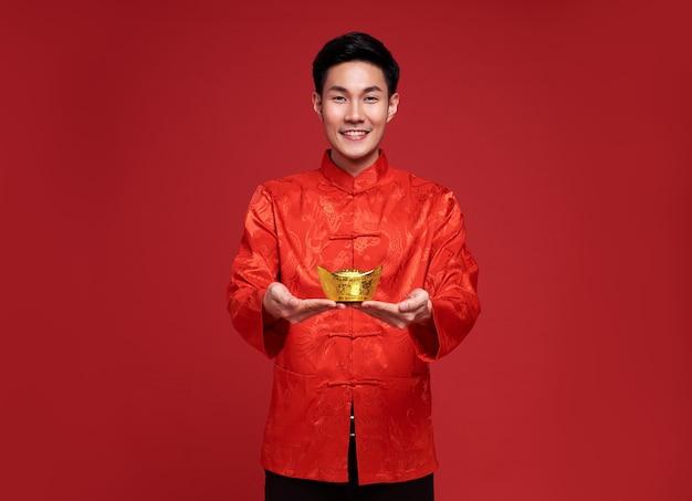 Gelukkig chinees nieuwjaar. aziatische man die in traditionele klederdracht draagt ?? die goudstaaf op rood houdt.