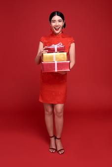 Gelukkig chinees nieuwjaar. aziatische vrouw, gekleed in traditionele cheongsam qipao jurk met geschenkdoos geïsoleerd op rode achtergrond.