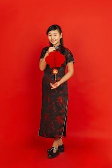Gelukkig chinees nieuwjaar. het portret van het aziatische jonge meisje dat op rode achtergrond wordt geïsoleerd. vrouwelijk model in traditionele kleding ziet er gelukkig uit en lacht met decoratie. viering, vakantie, emoties.