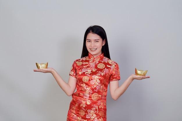 Gelukkig chinees nieuwjaar. portret mooie jonge aziatische vrouw draagt chinese jurk met goudstaven geïsoleerd in grijze studio achtergrond