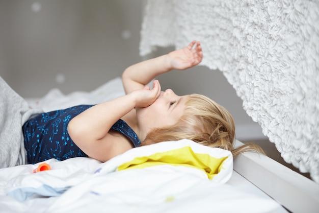 Gelukkig concept kindertijd. schattige kleine jongen met blond haar liggend op bed in zijn witte gezellige slaapkamer en spelen met zijn handen.