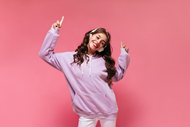 Gelukkig cool meisje in paarse oversized hoodie wijst naar boven en lacht breed