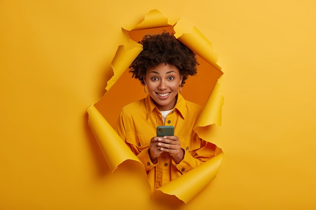 Gelukkig curly haired student lacht om grappige grap in sociale netwerken, glimlacht toothily, speelt spel online op moderne mobiel, gekleed in stijlvolle outfit, staat in gescheurde gat achtergrond