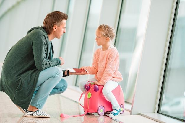 Gelukkig dada en meisje met instapkaart op luchthaven