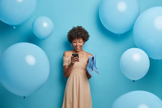 Gelukkig dag en feest concept. positieve donkere vrouw chats in sociale netwerken, draagt een lange beige jurk en houdt blauwe schoenen vast, kiest de beste outfit om er briljant uit te zien, geïsoleerd op blauwe muur