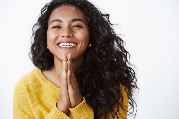 Gelukkig dankbaar jong schattig meisje bedankt voor hulp, erg blij dat je een mooi cadeau ontvangt, vrolijk lacht, handpalmen tegen elkaar drukt in gebed, staande witte muur in gele trui