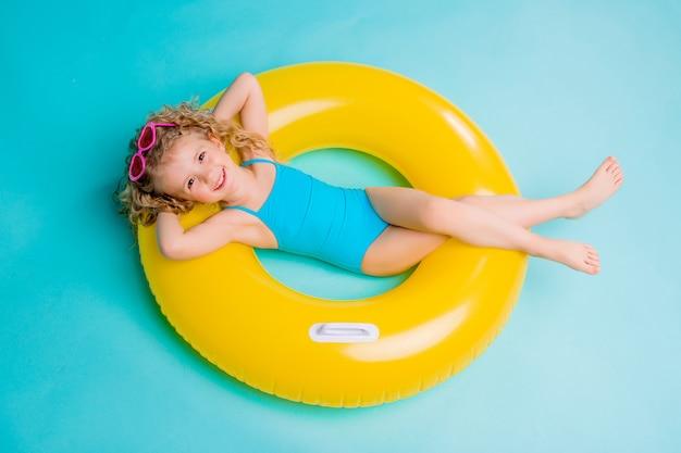 Gelukkig die babymeisje in zwempak met cirkel op blauwe achtergrond wordt geïsoleerd