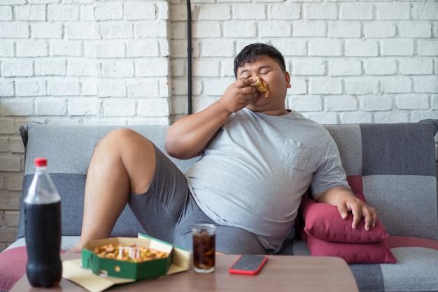 Gelukkig dikke man is blij tijdens het eten van pizza