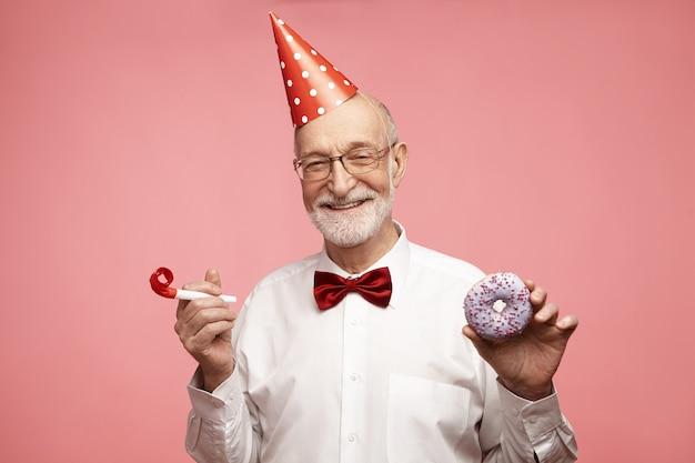 Gelukkig dolblij extatische volwassen zeventigjarige man met rode kegel hoed