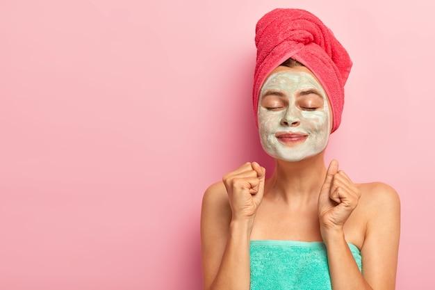Gelukkig dolblij vrouw past gezichtskleimasker toe, heeft een verjongingsbehandeling, balt beide vuisten, draagt een handdoek, houdt de ogen gesloten, geïsoleerd op roze studiomuur