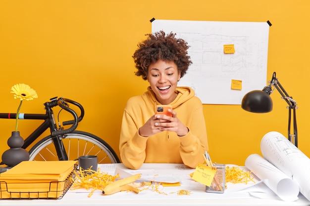 Gelukkig donker gevilde vrouwelijke student met krullend afro-haar doet hometask maakt rapport trekt schetsen draagt sweatshirt pose in coworking space