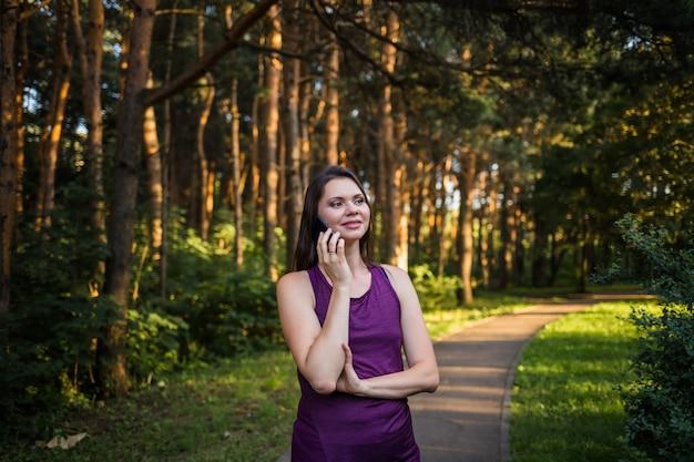 Gelukkig donkerbruin meisje dat op de telefoon in het park bij zonsondergang spreekt