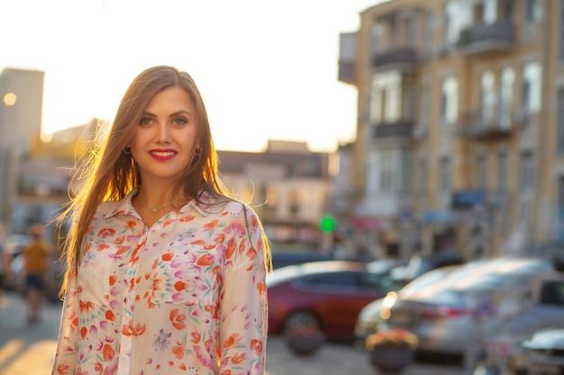 Gelukkig donkerbruin model die blouse en roze jasje dragen die bij de achtergrond van de avondstad stellen. ruimte voor tekst