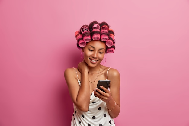 Gelukkig donkere huid volwassen vrouw met haarrollers, maakt kapsel bij speciale gelegenheid, gekleed in jurk, houdt mobiele telefoon vast, leest nieuws op internet, scrollt nieuws,