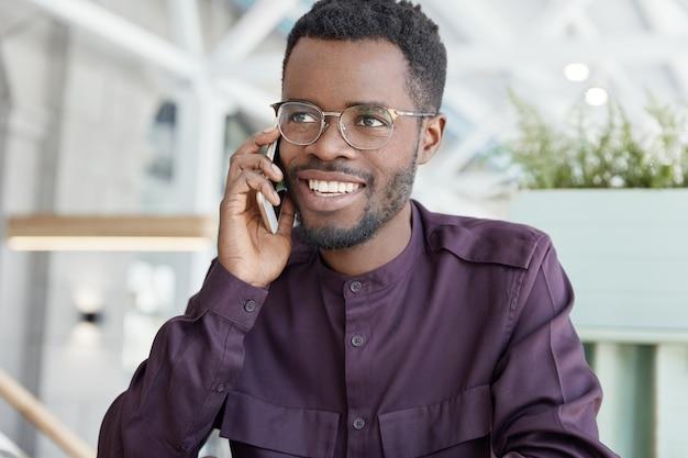 Gelukkig donkere jonge man met een positieve uitdrukking, brede glimlach, gekleed in formele kleding, heeft telefoongesprek met zakenpartner