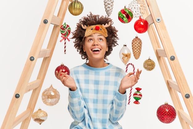 Gelukkig donkere vrouw kijkt positief boven op kerstballen en nieuwjaarsspeelgoed gekleed in pyjama en slaapmasker verspreidt palmen geniet van wintervakantie siert huis geniet van huiselijke sfeer.
