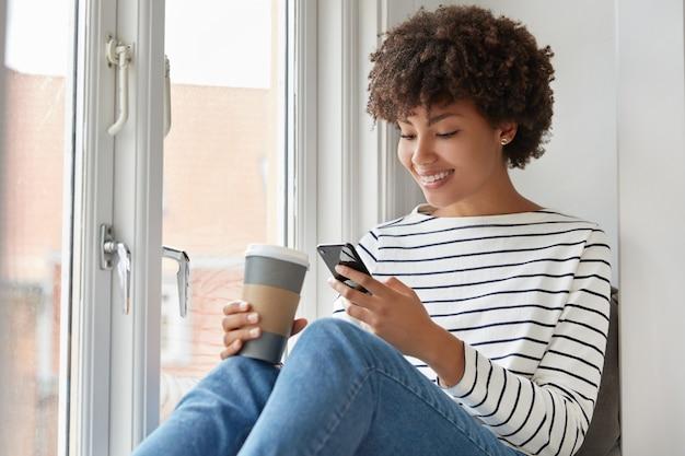 Gelukkig donkere vrouw met tevreden uitdrukking, leest online boek via mobiele telefoon, controleert e-mail in sociale netwerken