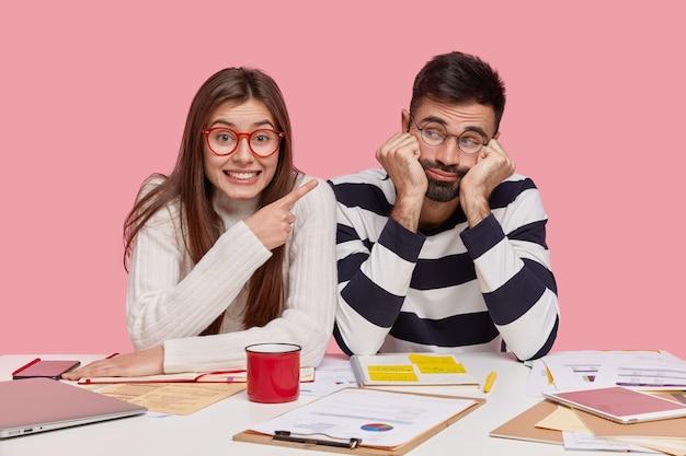 Gelukkig donkerharige jonge vrouw draagt doorzichtige bril, wijst naar trieste ongeschoren man, ontmoet elkaar voor preapring thuistoewijzing, pose op de werkplek