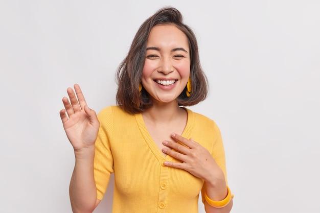 Gelukkig donkerharige mooie aziatische vrouw met positieve uitdrukking lacht vreugdevol houdt hand opgeheven glimlacht breed draagt gele jumper oorbellen hoort iets grappigs geïsoleerd over witte muur