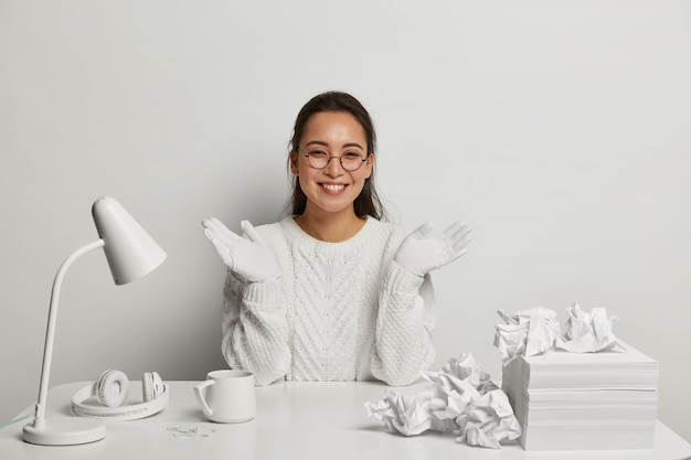 Gelukkig donkerharige vrouw administratief manager draagt nette witte trui en handschoenen