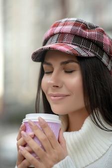 Gelukkig donkerharige vrouw die lacht terwijl haar heerlijke koffie ruikt