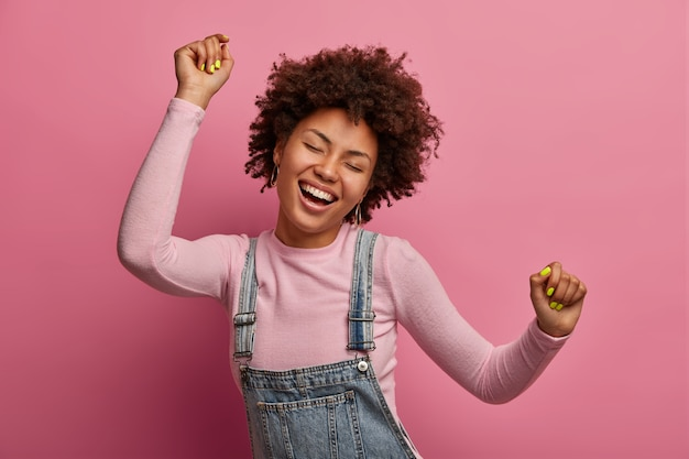 Gelukkig donkerhuidig meisje geniet van elk moment van het leven, danst en beweegt, heft armen op en balt vuisten, sluit de ogen, heeft een goed humeur, draagt een sarafan denim en coltrui, geïsoleerd op een roze muur