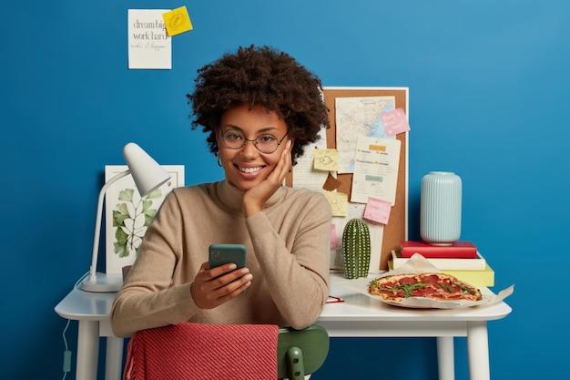 Gelukkig donkerhuidig meisje geniet van gratis high speed internet, gebruikt mobiele telefoon om te sms'en, zit tegen werkplek