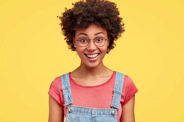Gelukkig donkerhuidige vrouw met afro-kapsel, heeft een tevreden uitdrukking, toont witte perfecte tanden, in een goed humeur na een date met vriendje, geïsoleerd over gele muur. emoties concept