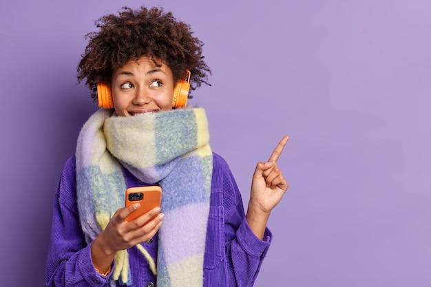 Gelukkig doordachte afro-amerikaanse vrouw omwikkeld met sjaal houdt mobiele telefoon heeft online communicatie luistert muziek via stereo hoofdtelefoon punten in de rechterbovenhoek toont lege ruimte voor tekst