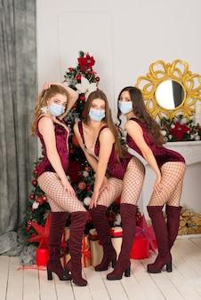 Gelukkig drie mooie meisjes in beschermend masker met verschillende haarkleur, sneeuwmeisje in kerstkostuums met cadeauzakje.